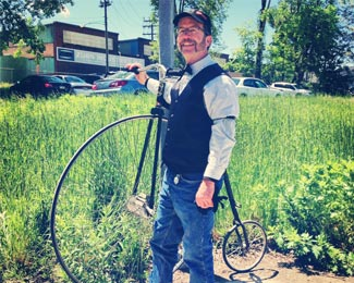 a man dressed in old time clothing standing next to an antique bicycle