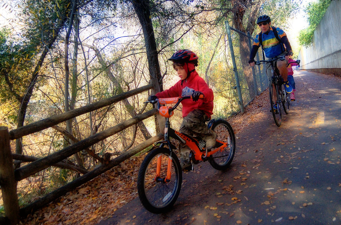 a man and his son ride bicycles on a paved trail